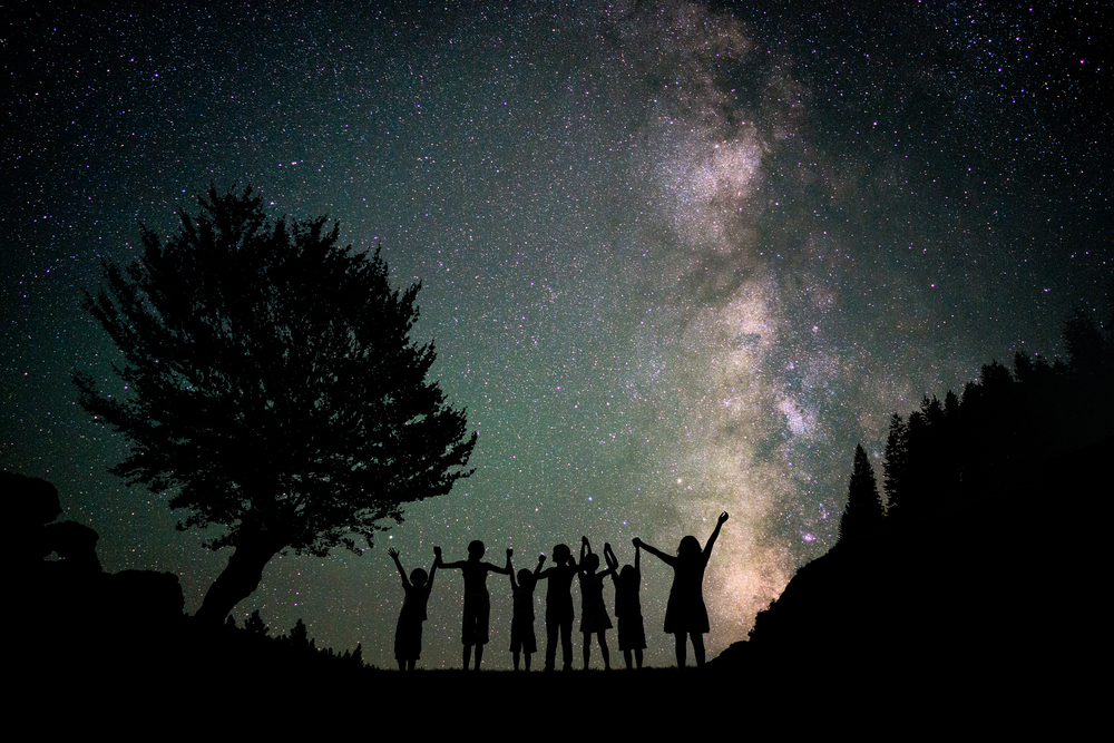 Happy kids group silhouette with Milky Way and beautiful night sky full of stars in background